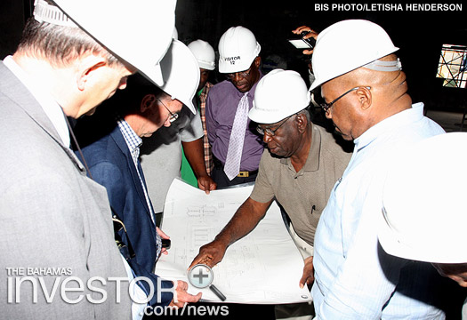 Minister of Public Works and Transport (first from right) and his team, inspect drawings of the new international airport under construction in Marsh Harbour