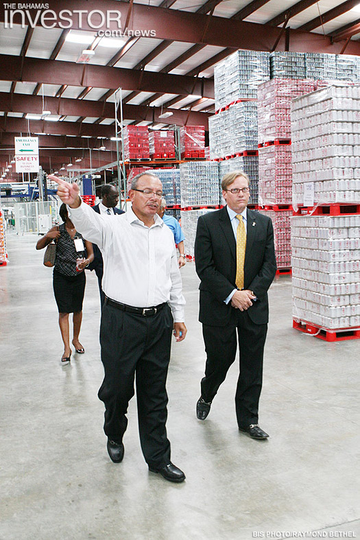 Minister of Financial Services Ryan Pinder (right) tours the new Coca-Cola plant July 19