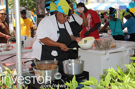 A vendor makes conch fritters for the crowds