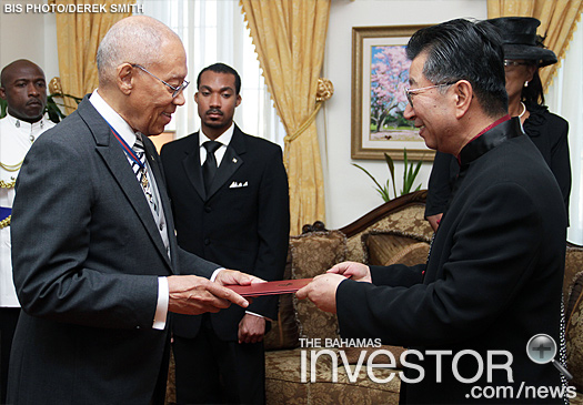 Sir Arthur Foulkes (left), accepts Letters of Credence presented by Ambassador Yuan Guisen